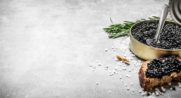 Vaso con caviale nero e panini. sul tavolo di pietra. spazio libero per il testo.