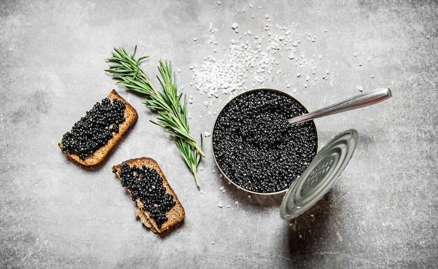 Vaso con caviale nero e panini sul tavolo di pietra