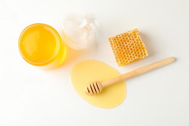 Vaso con miele, mestolo e nido d'ape su bianco Foto Premium