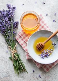 Vaso con miele e fiori di lavanda fresca su fondo di cemento
