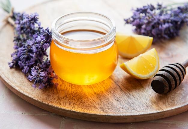 Vaso con miele e fiori di lavanda fresca su fondo in legno
