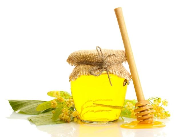 Vaso con miele di tiglio e fiori isolati su bianco