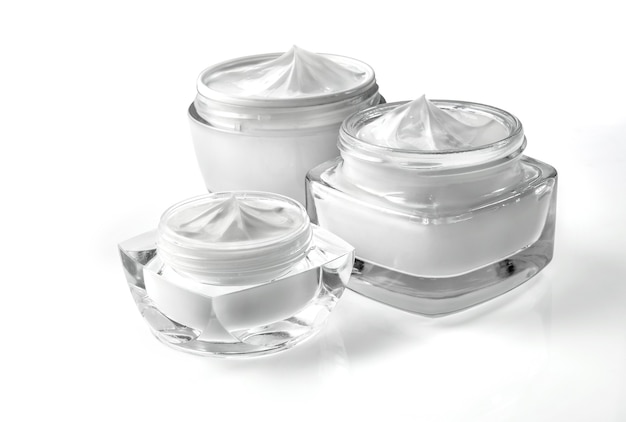 Vasetti di crema cosmetica isolati su bianco