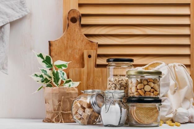 Barattoli pieni di ingredienti alimentari e vista frontale di fondo in legno