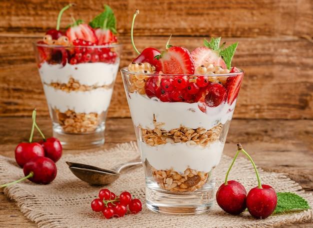 Vasetti di muesli con yogurt e bacche rosse sulla parete rustica in legno.