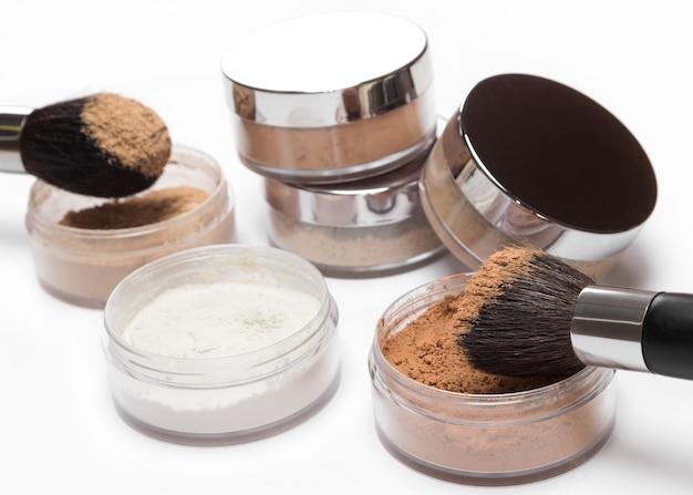 Vasetti di polvere cosmetica sfusa diversi colori e sfumature con pennelli per il trucco