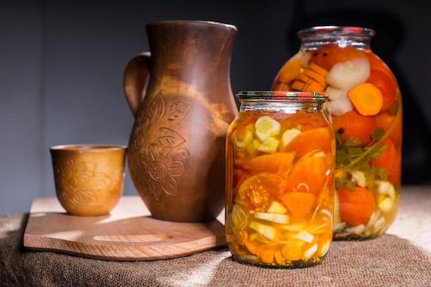 Barattoli di conserve di verdure sottaceto sulla superficie del tavolo accanto a oggetti di artigianato in legno intagliato - brocca, tazza, ciotola e tagliere in legno