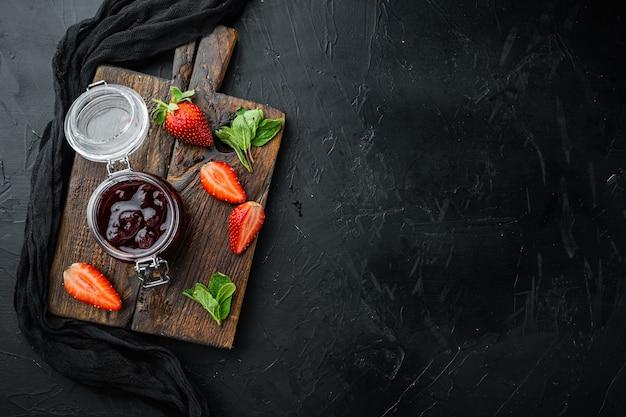Barattoli di marmellata di fragole con frutti di bosco, su sfondo nero, vista dall'alto piatta con spazio di copia per il testo
