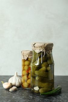Vasetti con cetrioli in scatola e olive sul tavolo smokey nero