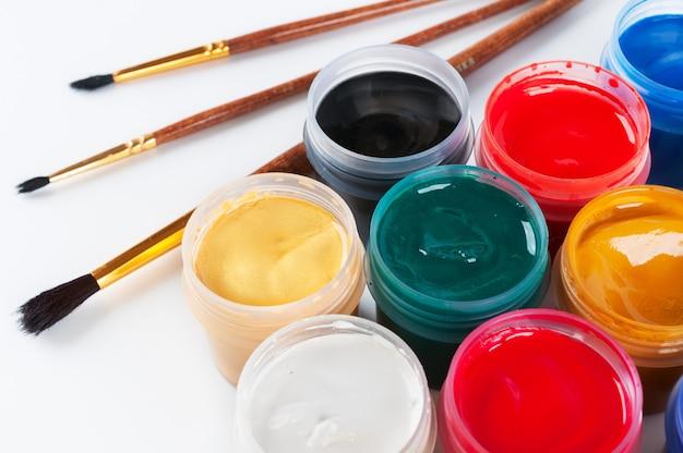 Vasetti con tempera colorata e pennelli. su uno sfondo bianco