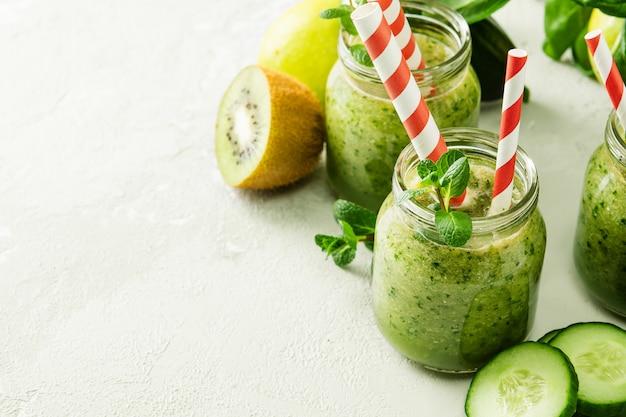 Vasetti con frullato verde e tubuli rossi su sfondo chiaro. frullato di verdure appena fatto. avvicinamento. vasetti di vetro con frullato verde su uno sfondo di cemento.