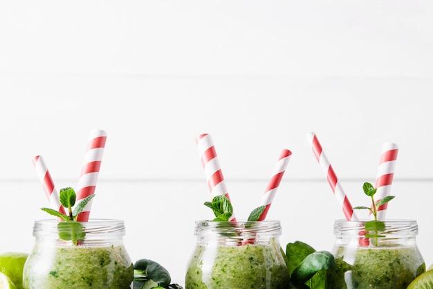 Vasetti con frullato verde e tubuli rossi su sfondo chiaro.