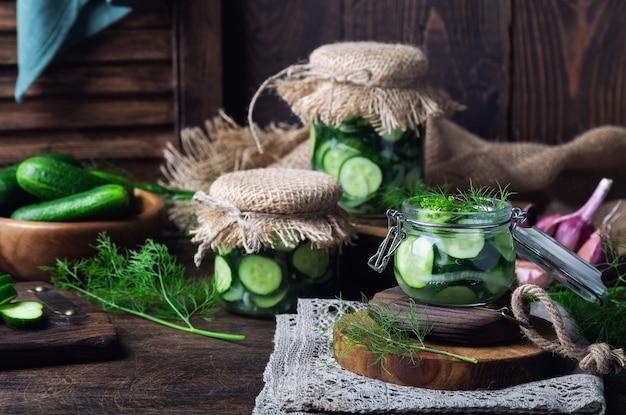 Vasetti con cetrioli sottaceto fatti in casa tagliati a fette con aneto e aglio su legno rustico.