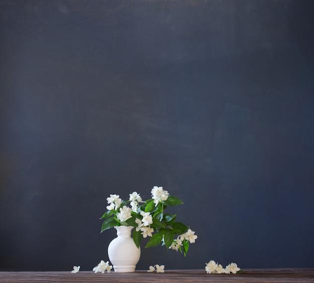 Fiori di gelsomino in vaso di ceramica su sfondo bianco