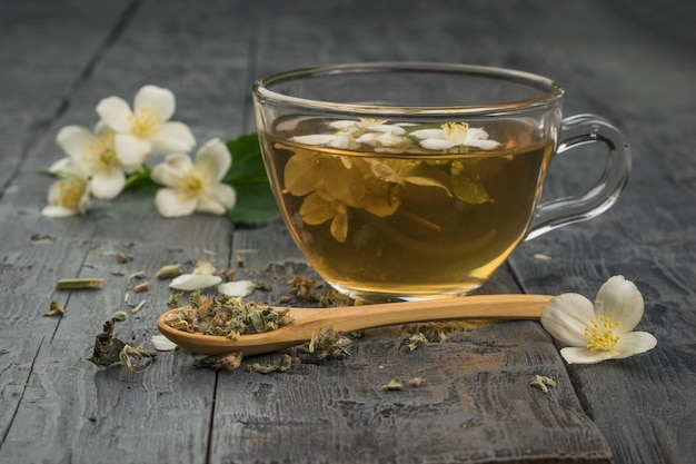 Fiori di gelsomino e tè ai fiori in una ciotola di vetro su un tavolo di legno. una tazza di tè ai fiori e un cucchiaio di legno con erbe secche.