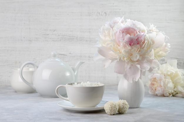 Tè al gelsomino e peonie bianche in vaso. natura morta bianca.