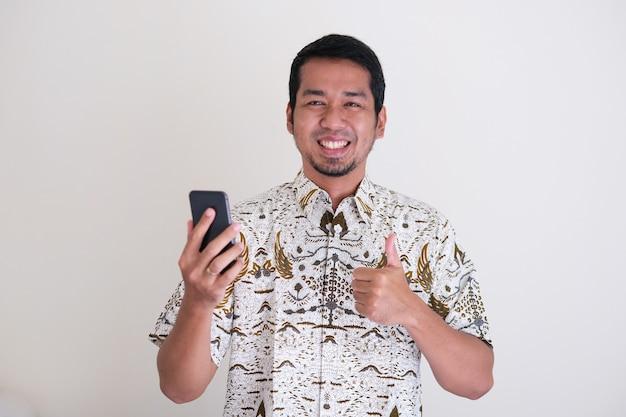 Uomo asiatico giavanese che sorride felice quando tiene il cellulare e dà il pollice in su