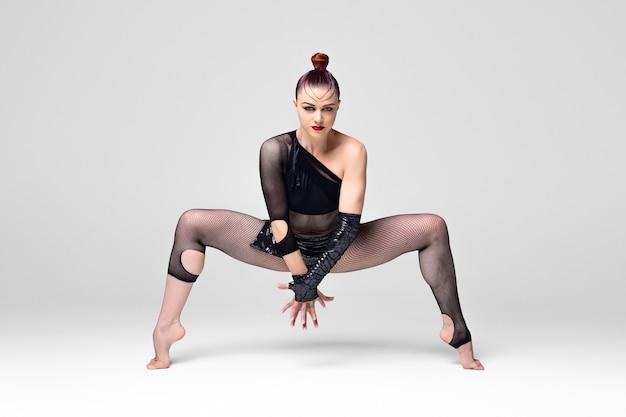 Ballerino moderno di jazz in una posa di danza espressiva. ballerina ragazza con trucco luminoso e un'acconciatura liscia in un vestito da spettacolo nero su sfondo bianco.