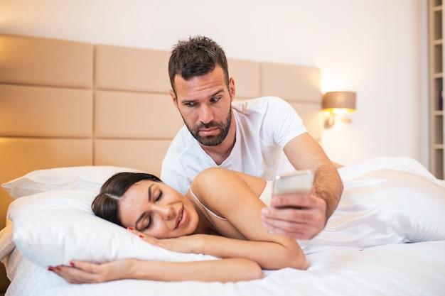 Marito geloso che spia il telefono della sua compagna mentre lei dorme in un letto di casa.