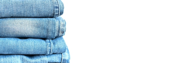I jeans sono impilati su uno sfondo bianco. pila di diverse donne alla moda o adolescenti pantaloni in denim casual per tutte le stagioni abbigliamento colore blu. striscione
