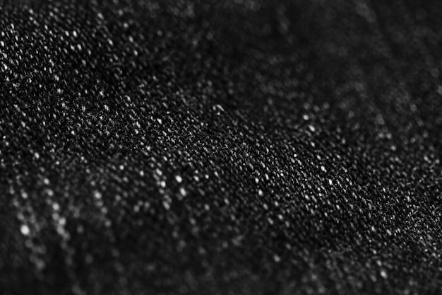 La fine di struttura del denim dei jeans su, mette a fuoco solo un punto, carta da parati del fondo blured molle