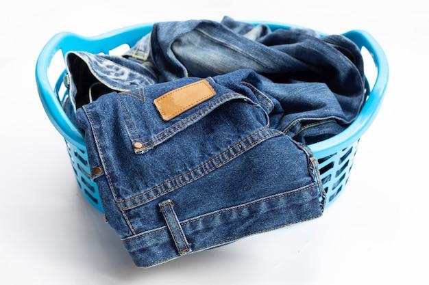Jeans nel cesto della biancheria su sfondo bianco.