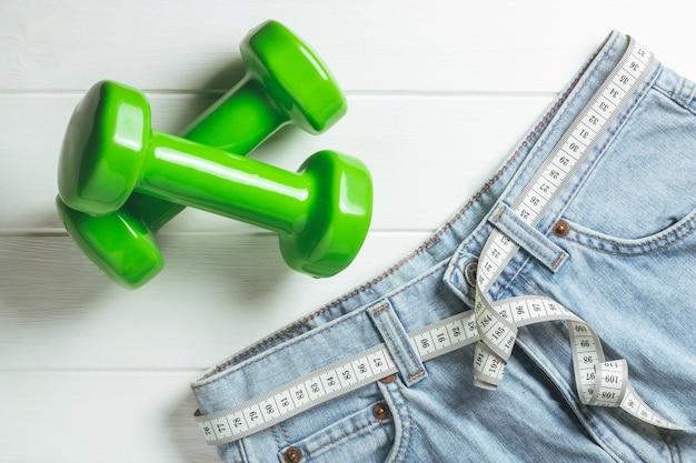 Jeans con nastro di misurazione invece di cintura e manubri verdi su superficie di legno bianca