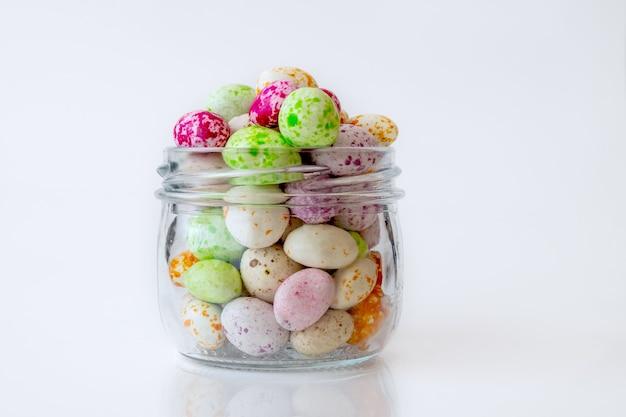 Spuntino della caramella di zucchero del fagiolo di gelatina in vaso di vetro alla moda isolato su bianco