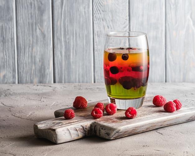 Dessert di gelatina con frutti di bosco in vetro sul vecchio tagliere di legno