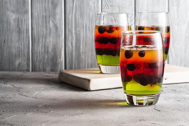 Dessert di gelatina con frutti di bosco in bicchieri sul vecchio tagliere di legno