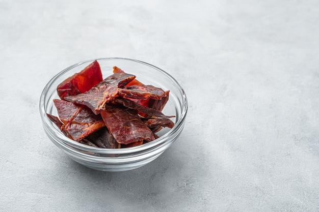 Fette di carne a scatti in una tazza trasparente su una parete grigio chiaro con spazio da copiare. cibo sano, snack naturale.