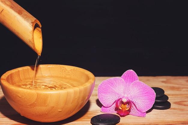 Il getto d'acqua viene versato dal bambù in una ciotola su un tavolo di legno, accanto alle pietre del trattamento termale e al fiore dell'orchidea, copia lo spazio per il testo.