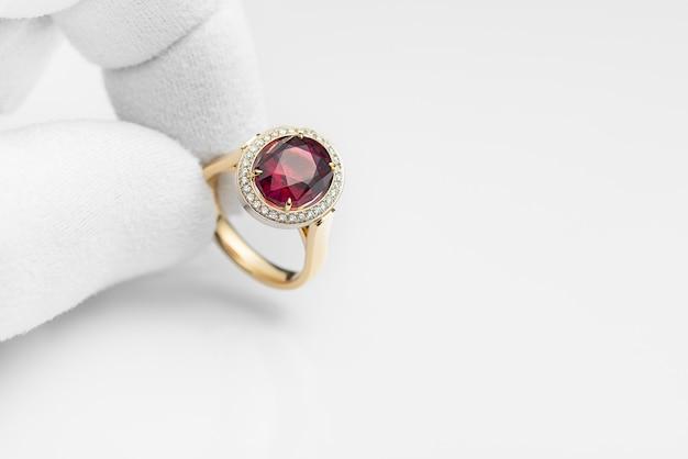 Gioielliere esaminando rubino o anello rodolite in officina, primo piano. anello in oro con rodolite e diamanti nella mano di un gioielliere