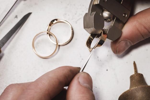Il gioielliere fissa le pietre in un anello d'oro