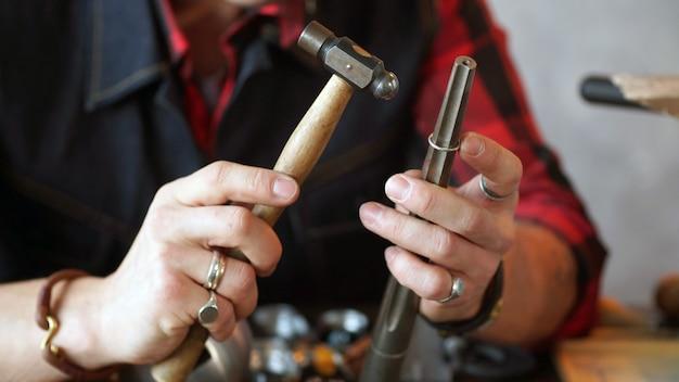 Gioielliere in mano con in mano un martello per fare gioielli. avvicinamento