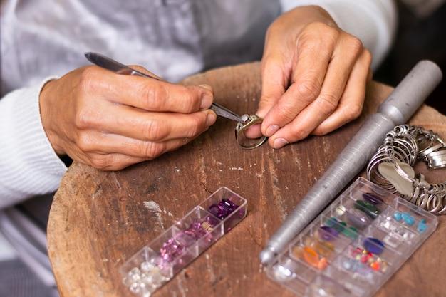 Mani del gioielliere che mettono un gioiello sulla vista alta dell'anello