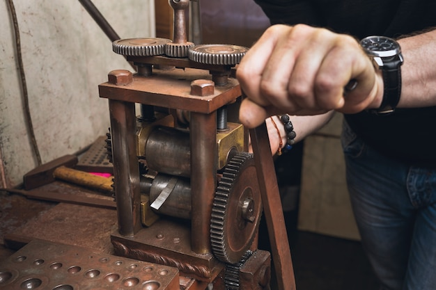 Un gioielliere arrotola un foglio di metallo per usarlo nel suo lavoro