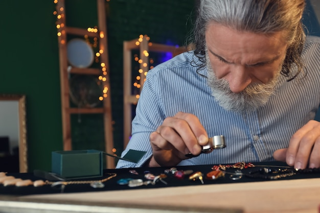Gioielliere esaminando ornamento in officina