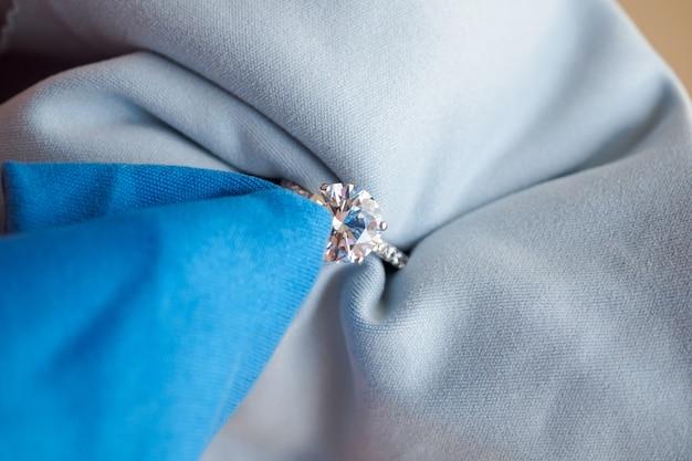 Gioielliere lucidatura a mano e pulizia anello di diamanti gioielli con tessuto in microfibra