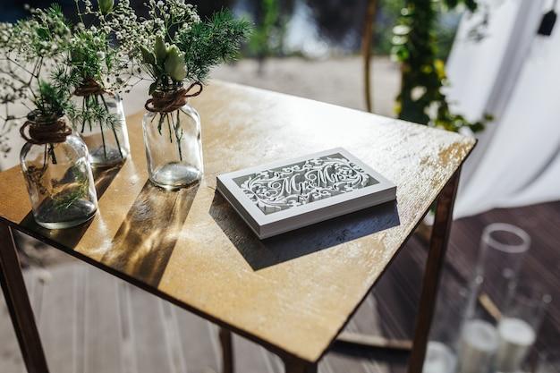 Portagioie per anelli sul tavolo con piccoli bouquet