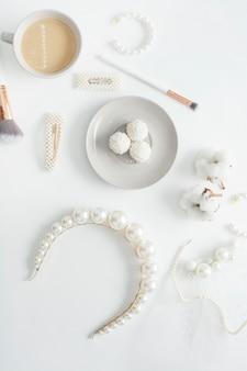 Gioielli per la sposa, perle, pennelli per il trucco, colori delicati, caramelle e caffè, su uno spazio bianco