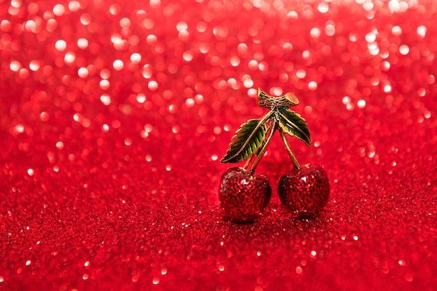 Coppia di gioielli di ciliegie su sfondo rosso
