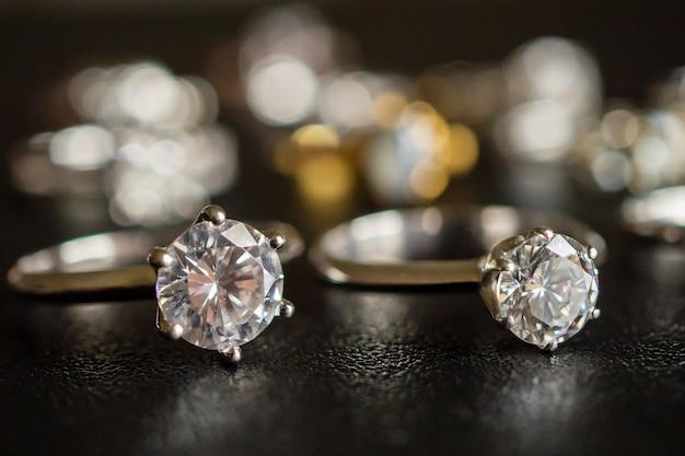 Anelli di diamanti gioielli incastonati su sfondo nero da vicino