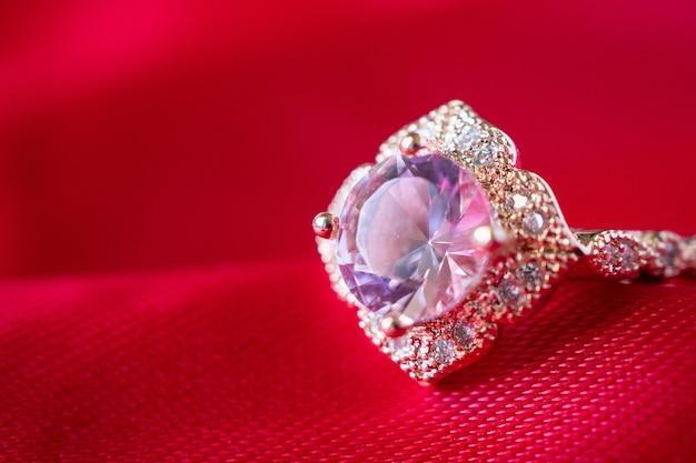 Anello in oro rosa di lusso di gioielli con gemma di zaffiro su sfondo rosso trama di tessuto