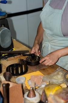 Donna del creatore di gioielli che lavora nel laboratorio di gioielli professionale al suo banco di lavoro.