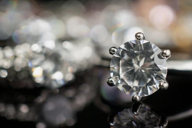 Anelli di diamanti di nozze gioielli sul nero con la riflessione