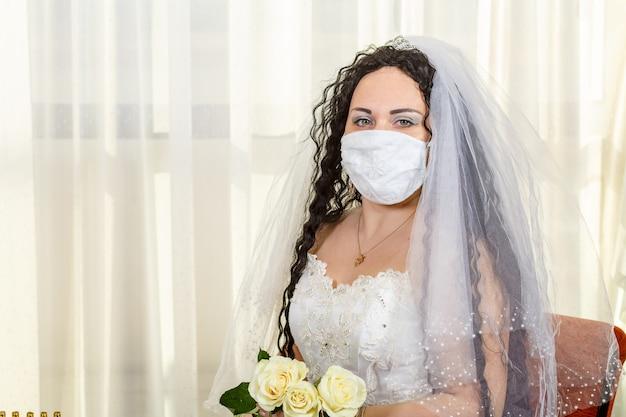 Una sposa ebrea siede in una sinagoga prima di una cerimonia di chuppa durante una pandemia, indossando una maschera medica e un mazzo di fiori. foto orizzontale