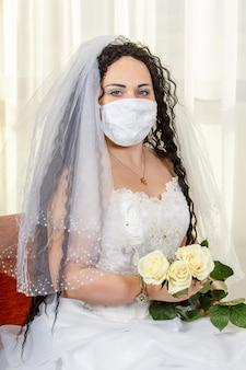 Una sposa ebrea siede fino alla cintola in una sinagoga prima di una cerimonia di chuppa durante una pandemia, indossa una maschera medica e un mazzo di fiori, attende lo sposo. foto verticale