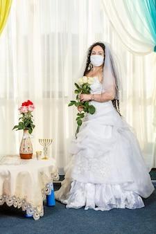 Una sposa ebrea siede fino alla vita in una sinagoga a un tavolo con fiori prima di una cerimonia di chuppa durante una pandemia, indossa una maschera medica e un mazzo di fiori, attende lo sposo. foto verticale