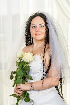 Una sposa ebrea è in piedi nella sala prima della cerimonia della chuppa con un mazzo di rose bianche tra le mani, una foto fino alla vita. foto verticale